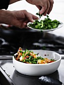 A man sprinkling chilli prawns with fresh coriander