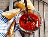 Homemade barbecue sauce in a jar with a spoon