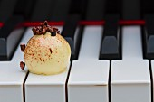 A white praline on the keys of a piano
