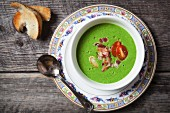 A bowl of cold courgette soup with roasted garlic, tomatoes and bacon