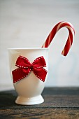 A candy cane in a white porcelain egg cup with a red bow