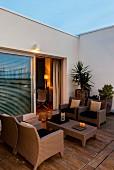 Abendstimmung auf mediterraner Terrasse, Sitzplatz mit Rattanmöbel