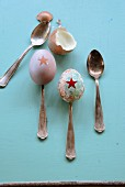 Easter eggs painted with star motifs on antique silver spoons