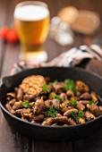 Fried chicken hearts with garlic and parsley in a pan with a glass of beer in the background