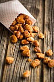 Homemade roasted almonds with a paper bag on a wooden surface