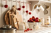 Fresh apples, baking ingredients and various kitchen utensils on dresser