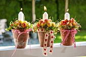 Candles and crab apples arranged in plant pots