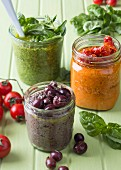 Pesto with black olives, herb pesto, red pesto