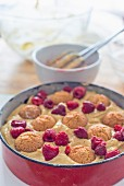Unbaked amaretti and raspberry cake in a baking dish