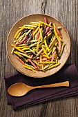 Colourful pasta in a wooden bowl (seen from above)