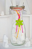 White marshmallow hearts in glass bottle decorated as gift