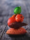 A stack of vegetables: sweet potato, pumpkin, tomato and courgette