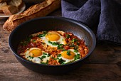 Fried eggs with tomatoes, peppers and onions
