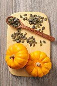 Pumpkin seeds and mini pumpkins on a chopping board