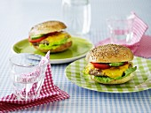 A cheeseburger with cucumber and tomatoes