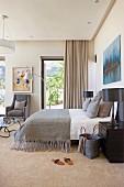 Doppelbett mit grauer Tagesdecke, auf Nachtkästchen schwarze Tischleuchten in elegantem Schlafzimmer