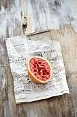 A halved blood orange on a newspaper