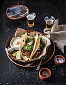 Tacos with beef ribs, pepper, salt, sour cream and beer