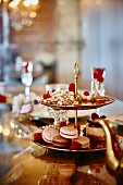 Macaroons, tartlets and raspberries on an elegant cake stand