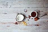 Superfood: Kokosnuss, Kakao & Gojibeeren auf Holzuntergrund (Aufsicht)