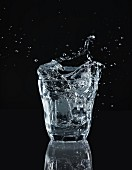 Water splashing from a glass against a black background