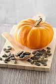 A mini pumpkin and pumpkin seeds on a chopping board