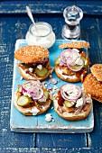 Burger mit Schweinefleisch, Essiggurken, Meerrettichsahne, roten Zwiebeln und Feta