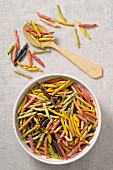 Colourful pasta in a bowl and next to it (seen from above)