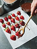Strawberries being drizzled with chocolate