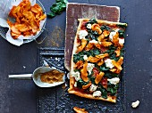 A pizza with spinach and root vegetable crisps
