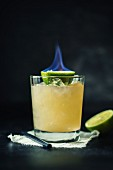 A Mai Tai garnished with a flambéed lime