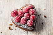A mini heart-shaped chocolate cake with raspberries (gluten free)