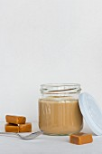 Cooked caramel pudding in a jar with a lid and a spoon