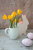Crocuses in milk jug, Easter egg decorations and paper Easter bunnies
