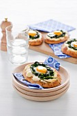 Naan pizzas with spinach, goat's cheese and fried eggs