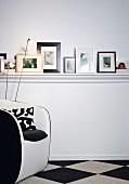 DIY-Wandboard mit weiß lackierter Profilleiste dekoriert mit verschiedenen, aufgestellten Bilderrahmen