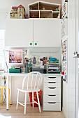 Weißer Schreibtischplatz mit Schubladenschrank und weißem Hängeschrank mit Puppenhaus in Mädchenzimmer