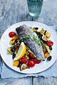 Trout on a bed of grilled vegetables with a lemon wedge