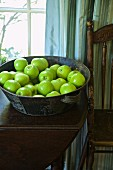 Green apples in a metal bowl on a wooden table in front of the window