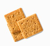 Three wheat crackers on a white surface (close-up)