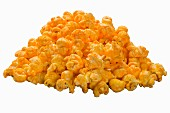 A pile of cheddar popcorn on a white surface