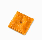 A cheddar cracker on a white surface (close-up)