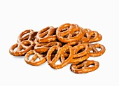 A pile of mini salted pretzels on a white surface