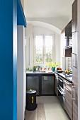 Schmale Küche mit blauer Wand