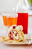 A slice of raspberry Swiss roll with flaked almonds