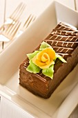 A slice of chocolate cake with a marzipan rose