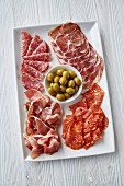An Italian antipasti platter with ham, salami and olives