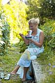 Frau isst Tomatensalat mit Feta im Garten