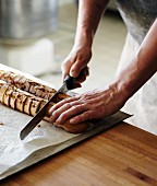 A baker slicing crusty bread