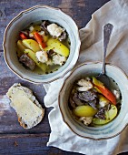 Beef soup with dumplings and vegetables served with a slice of bread and cheese